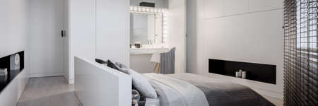 Panorama of elegant, black and white bedroom with big bed and stylish dressing table with light bulbs around mirror