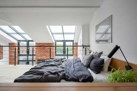 Simple bedroom on mezzanine in loft style apartment with big windows and exposed red brick on the wall