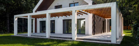 Panorama of exterior view of modern, white house with stylish veranda and green lawn in backyard