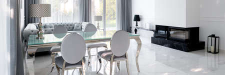 Panorama of elegant and glamorous living room with glass and fancy dining area, stylish fireplace and quilted sofa