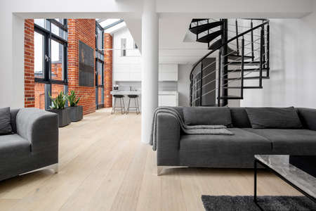 Beautiful loft apartment with exposed red brick on the walls, big windows, stairs and kitchen open to living room with modern gray furniture