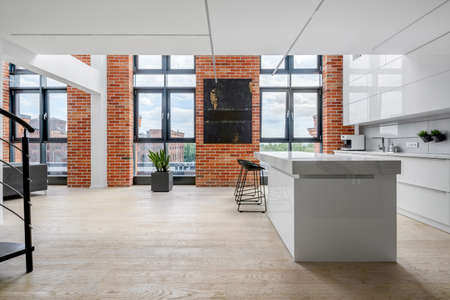 Spacious white kitchen in stylish loft apartment with exposed brick on the walls and big windows