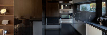 Panorama of elegant kitchen with mirrored black cupboards and oven with microwave build in wall