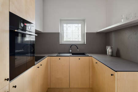 Elegant kitchen with birch plywood on furniture, dark veneer countertops, black sink and tap and one small window