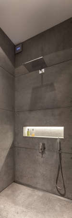 Vertical panorama of modern designed bathroom with shower in stylish concrete wall tiles