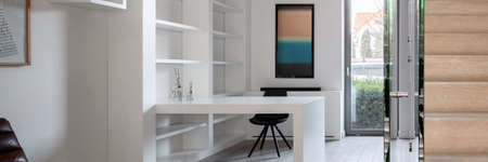 Panorama of simple home office with white shelves, walls and desk and wooden stairs Imagens