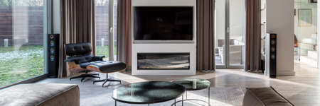 Panorama of stylish design in room with big television screen and modern fireplace