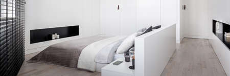 Panorama of simple white bedroom with white walls and wardrobe, white frame double bed, wooden floor and big window with black blinds