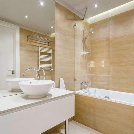 Elegant bathroom with beige tiles, stylish washbasin, big bathtub and shower and ceiling light Stock fotó