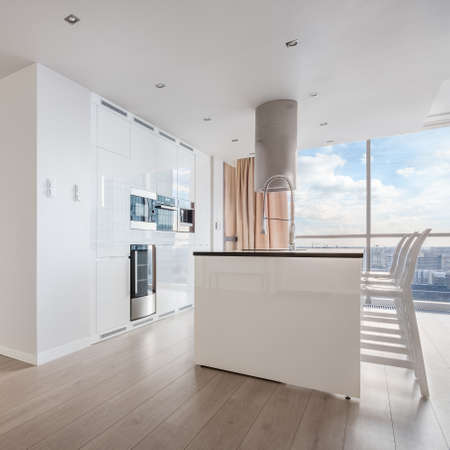 White shiny kitchen with big kitchen island and exhaust hood in apartment with amazing city view