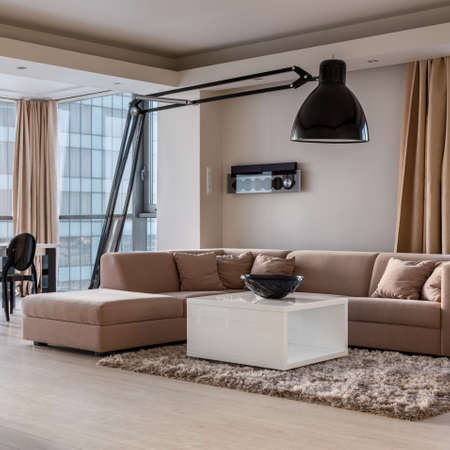 Luxury beige corner sofa in stylish living room with square, white coffee table and modern big black lamp