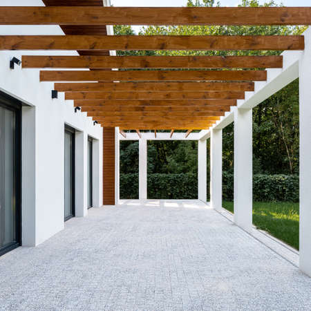 Wooden beams on ceiling in terrace of modern white home, exterior
