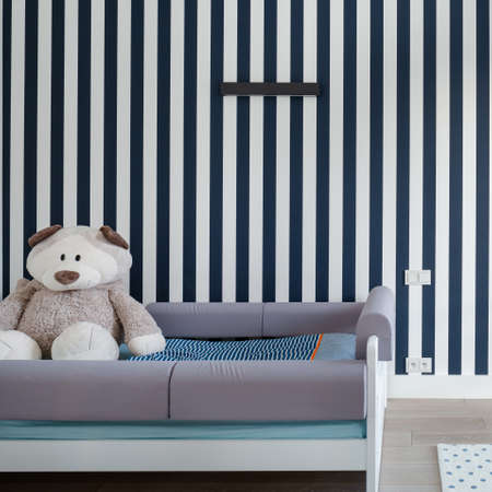 Stylish baby room with blue stripes on the wall and small bed with bog teddy bear