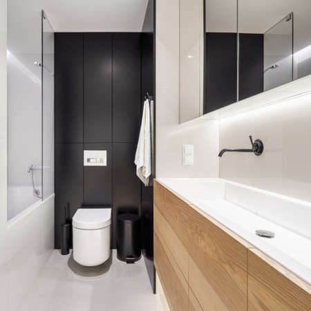 Stylish bathroom with long washbasin, black wall behind toilet and bathtub with shower