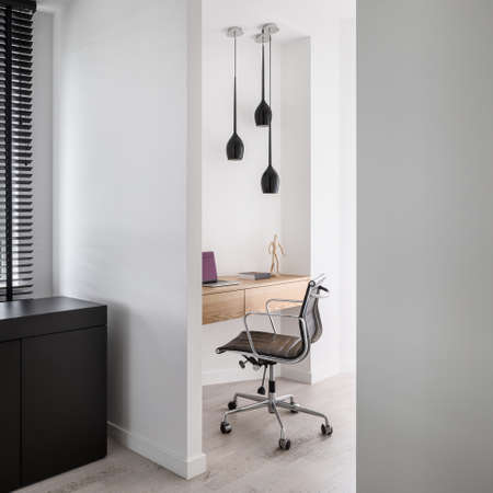 Stylish and simple home office and study area with wooden desk and comfortable chair