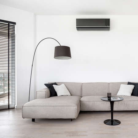 Stylish and modern living room with air conditioner and simple corner sofa with black coffee table and lamp