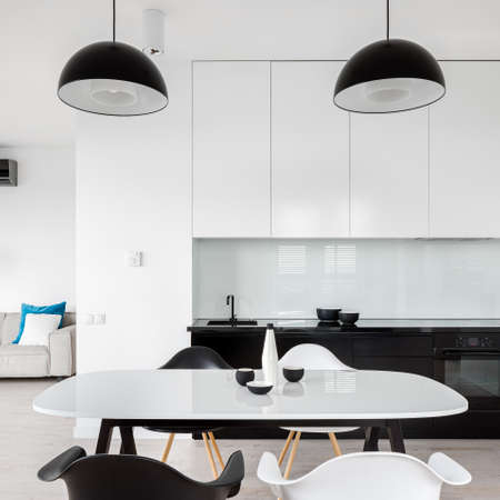 Modern black and white kitchen with white dining table and four chairs open to living room Imagens