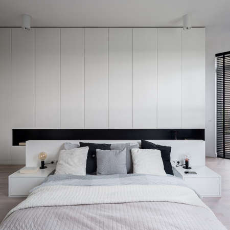 Modern white bedroom interior with big and comfortable bed, white bedside tables and headboard