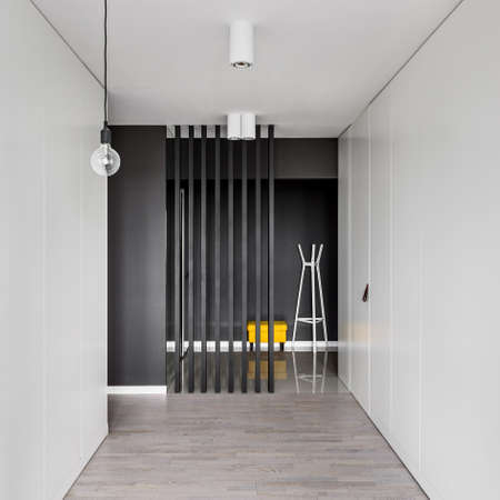 Modern corridor interior with white wardrobes and black area with yellow seat and white clothes hanger Imagens