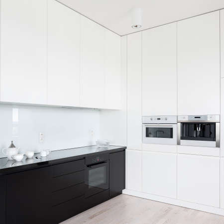 Modern and stylish kitchen interior with white walls and upper cupboards and black countertops, drawers and lower cupboards Imagens