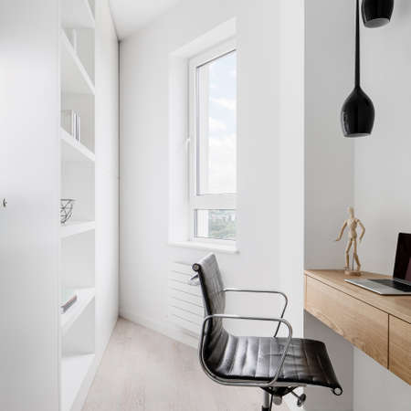 Simple white home office interior with wooden desk, black chair and window