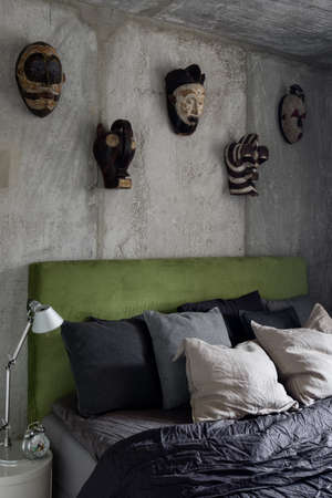Bedroom with concrete wall and ceiling, decorative masks and comfortable bed with simple nightstand and lamp Imagens