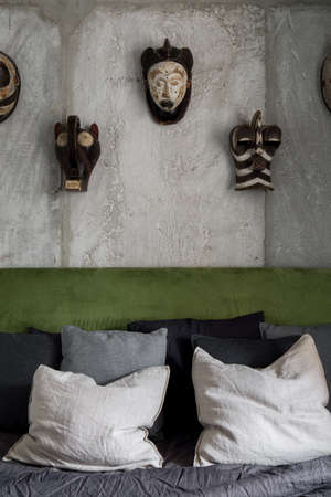 Bedroom with bare concrete on the wall behind bed and decorative african masks