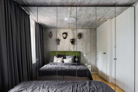 Modern designed bedroom with mirror wardrobe, exposed concrete on walls and ceiling and big comfortable bed