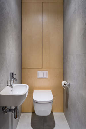 Simple bathroom in gray floor and wall tiles, small washbasin and wooden wall behind toilet