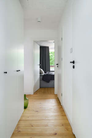 Simple white corridor with wooden floor, white doors and wardrobe with black handles