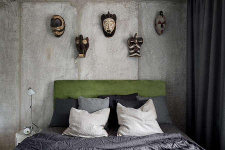 Bedroom with bare concrete and african masks on wall behind bed with green velor on headboard Imagens