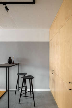 Modern and simple black table with two bar stools in kitchen with birch veneer on cupboards and exposed concrete on walls and ceiling Imagens