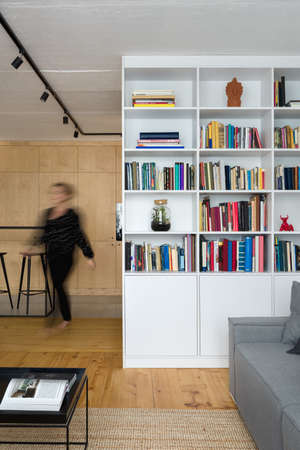 Woman in stylish apartment with white bookcase, wooden floor and concrete ceiling