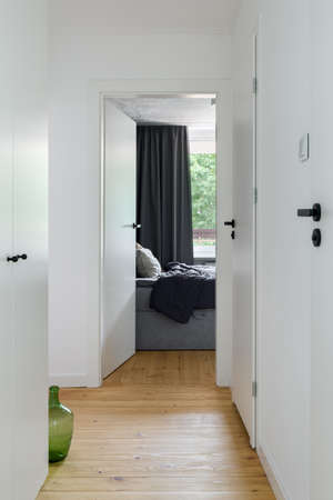 Modern, white apartment corridor with white doors and black door handles, wooden floor and bedroom doors open