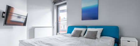 Panorama of modern bedroom with double blue bed, television screen and art on the wall and big window Imagens - 156817501