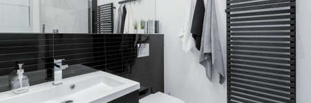 Panorama of simple black and white bathroom with big mirror, long washbasin and modern black wall tiles Imagens