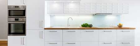Panorama of modern kitchen with white furniture, wooden countertop and build in fridge, oven and microwave