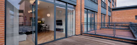 Panorama of elegant balcony with wooden floor in building with red brick walls and big window open to modern loft apartment Imagens - 156817505
