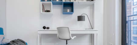 Panorama of teen room in white and blue with simple desk to study and square wall shelves Imagens - 156817506