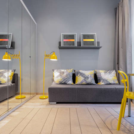 Modern room interior with gray walls and sofa, wooden floor, mirrors on wardrobe and yellow decorative details Imagens