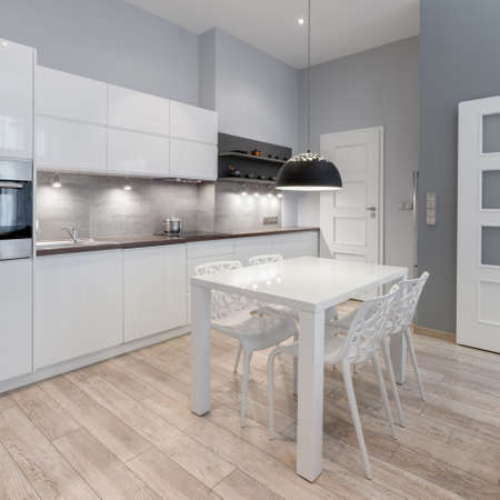 Simple and stylish kitchen with gray walls and wooden floor and white cupboards and drawers and modern white dining table with new white chairs