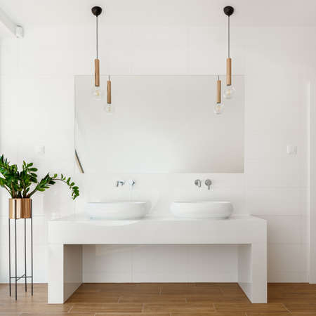 Luxury white bathroom with big mirror above two washbasin and wooden floor