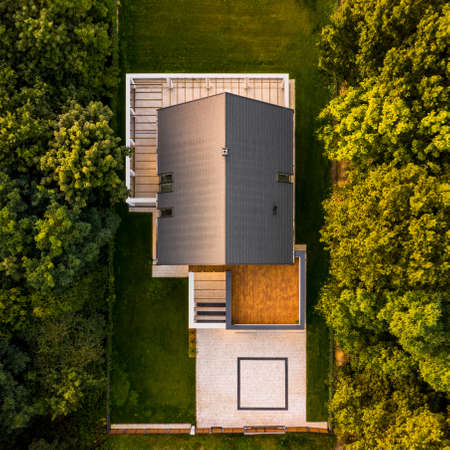 Drone view of big and modern house, with cobblestone driveway and wooden terrace in forest