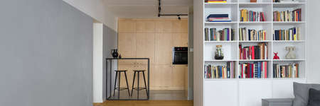 Panorama of apartment with kitchen open to room with white bookcase and decorative exposed concrete on gray wall