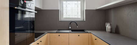 Panorama of elegant kitchen with birch plywood on furniture fronts, dark veneer countertops, oven, black sink with tap and one small window Standard-Bild
