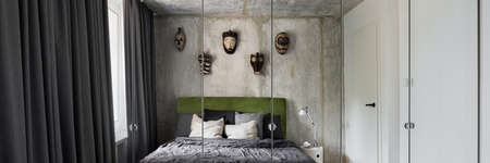 Panorama of modern designed bedroom with mirror wardrobe, exposed concrete on walls and ceiling, window behind gray curtains and big comfortable bed under african decorative masks