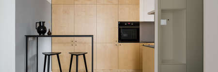 Panorama of modern style kitchen with birch plywood cupboards and black table with tall bar stools