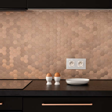 Breakfast on black countertop in stylish black kitchen with elegant, golden hexagonal shaped wall tiles