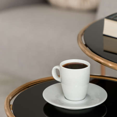 Close-up on white cup of coffee on stylish coffee table with black top and golden frame