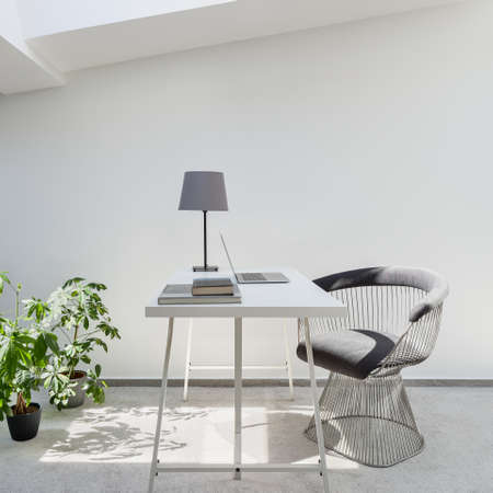 Simple home office space to work or study on the attic with white walls and gray carpet flooring